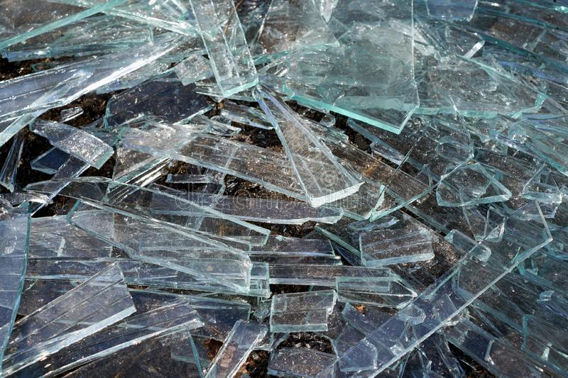 A pile of different sharp pieces of broken glass lying on the ground. Pieces of glass of different size and shape. Many pieces of oblong shape. The sharp edges royalty free stock photography