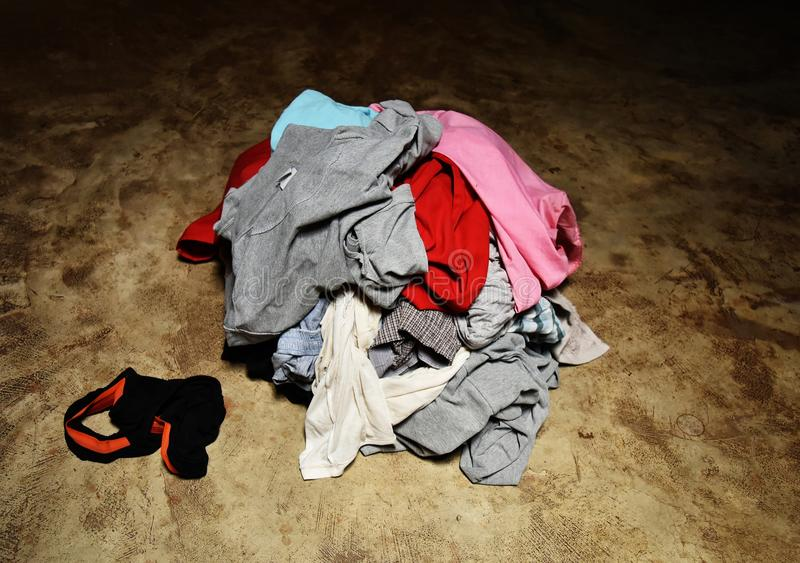 Pile of dirty clothes in green basket on cement ground stock images