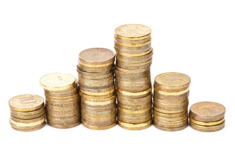 Pile dorate delle monete in una riga fotografie stock libere da diritti