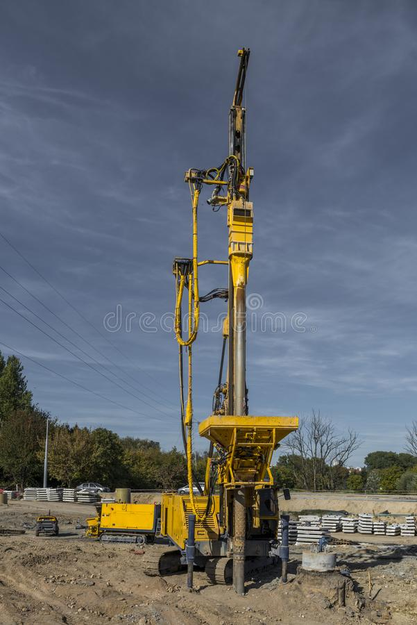 Pile driving drilling machine working on road construction. Road building with drilling machine. Drilling machine ready to drill piles on a road building site stock images