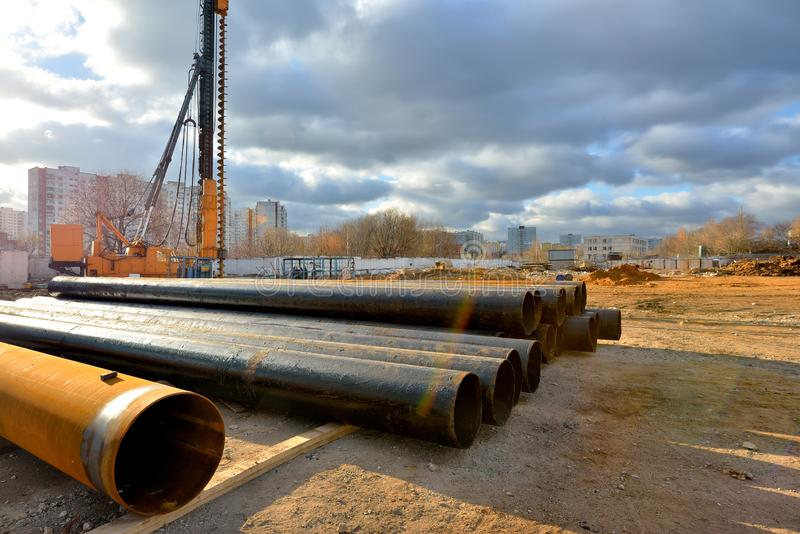 Pile driving machine and metal pipes on a construction site.  royalty free stock photo