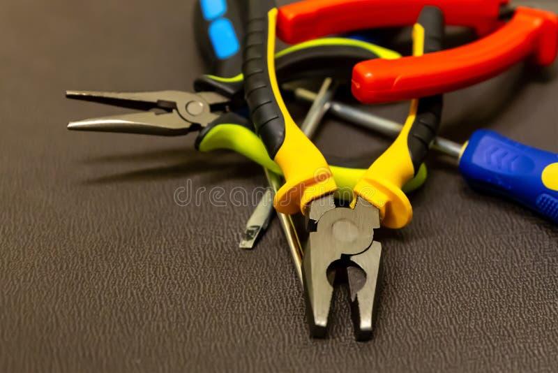 Pile du plan rapproché de tournevis de coupe-fil d'un bon nombre de pinces de style grunge d'outils de bricolage sur la base fonc photos stock