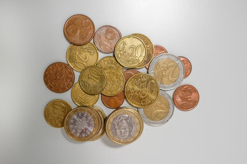 Pile of Euro and cents coins of various denominations on a white desk, top down view royalty free stock image