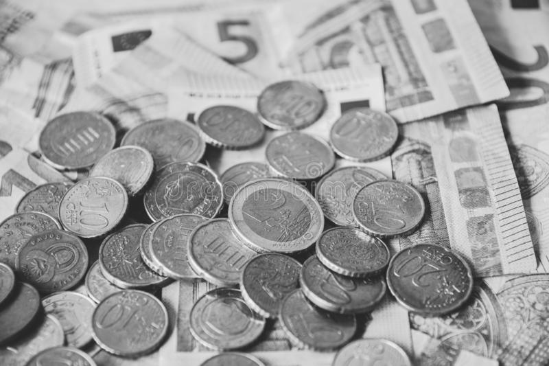 Pile of Euro coins on euro bank money notes of 5, 10 and 20 euro. Finance and economy. Black and White editing royalty free stock photo