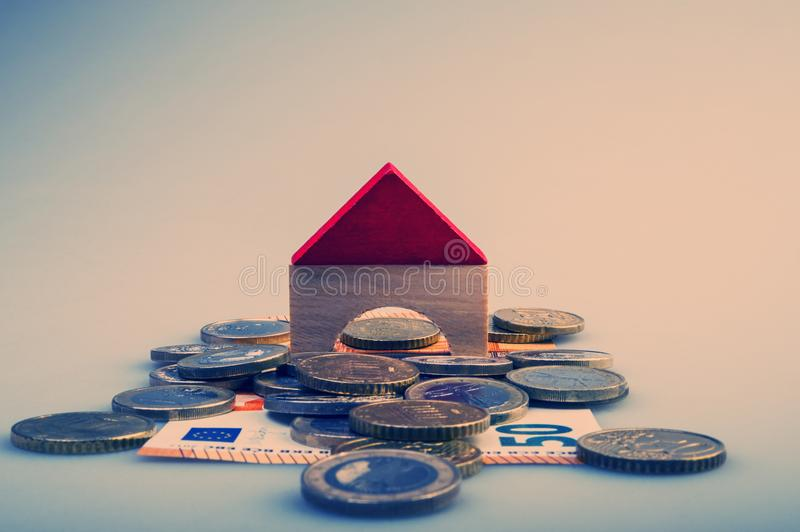 Pile of euro coins and paper bills and a house layout on a light stock photography