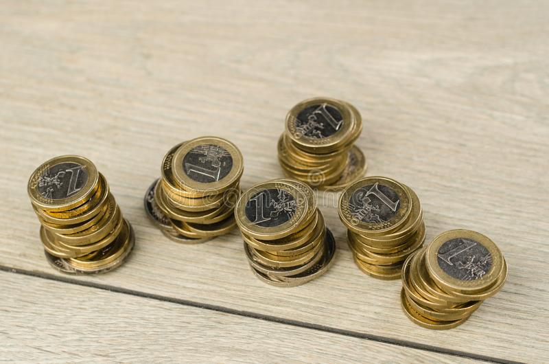 Pile of 1 Euro coins. Six piles of 1 euro coins on wooden floor in studio stock photography