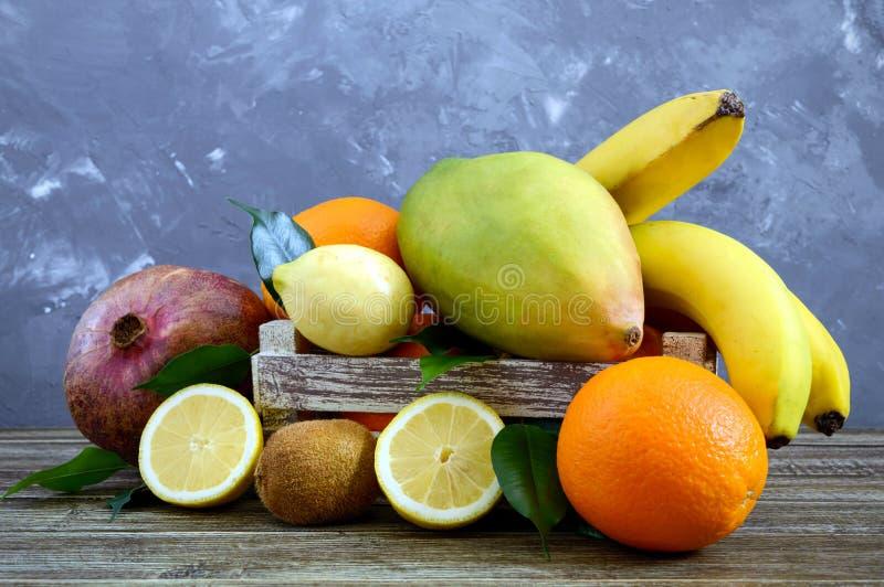 A pile of exotic fruits bananas, oranges, kiwi, pomegranate, mango, guava, lemon royalty free stock photos