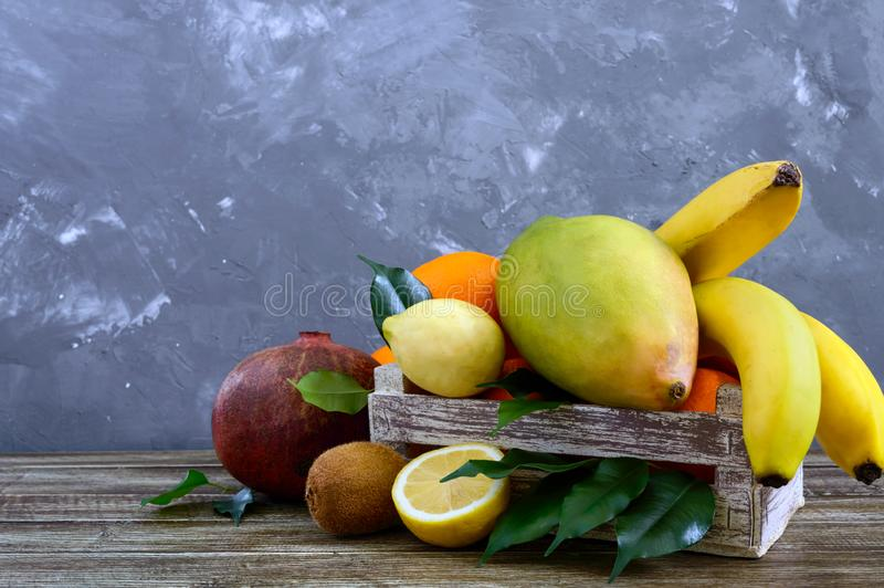 A pile of exotic fruits bananas, oranges, kiwi, pomegranate, mango, guava, lemon in a wooden box stock photo