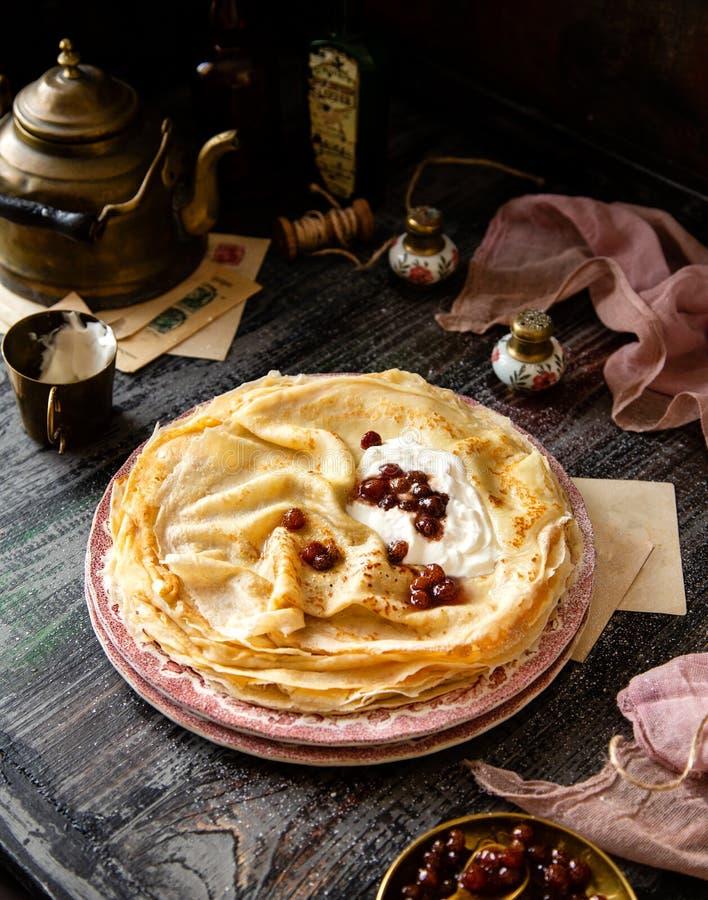 Pile faite maison de crêpes minces avec la crème sure et la confiture rouge des plats de rose de cru photos stock