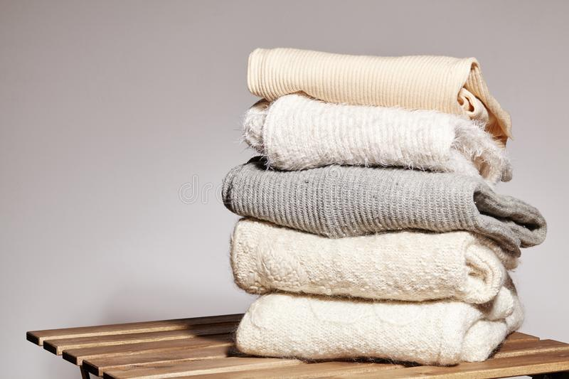 Pile of Fashion Warm Sweaters on Wooden Table. Autumn and Winter Wool Clothes. Knitted Sweater or Jacket. Tender Colors stock photography