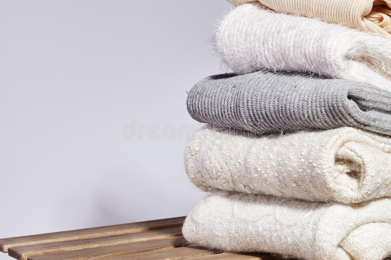 Pile of Fashion Warm Sweaters on Wooden Table. Autumn and Winter Wool Clothes. Knitted Sweater or Jacket. Tender Colors royalty free stock photos