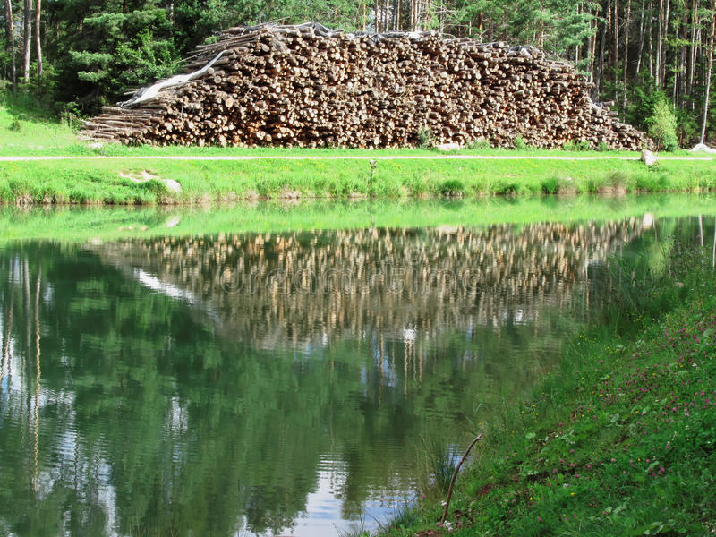 Pile of firewood in front of a small mountain lake . The woodpile is reflected on the lake. Fie allo sciliar, South Tyrol, Italy.  stock photos