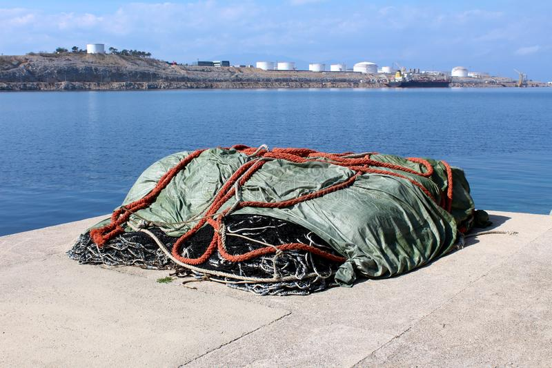 Pile of fishing nets covered with nylon protection during winter on concrete pier edge surrounded with sea and industrial complex. Pile of fishing nets covered stock photo