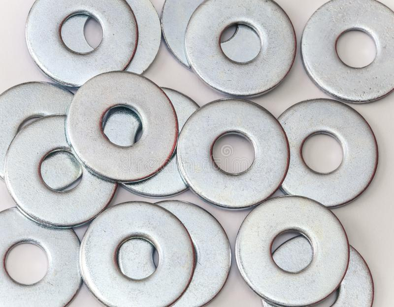 Pile of flat metal washers for screws and fasteners. On a white background stock photography