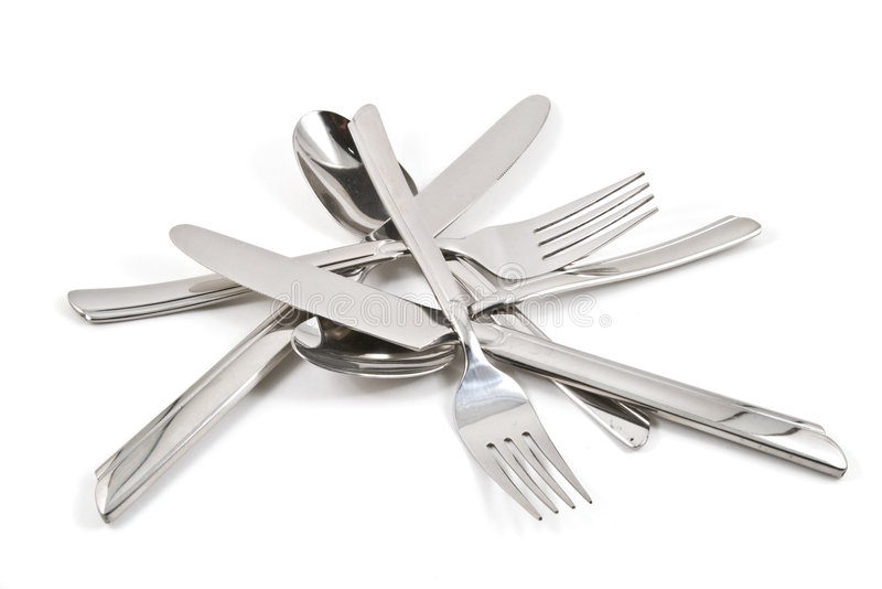 A pile of flatware. A pile of stainless steel flatware on a white background stock photo
