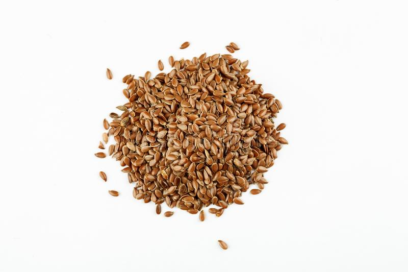 Pile of flax seeds on a white background.  stock images