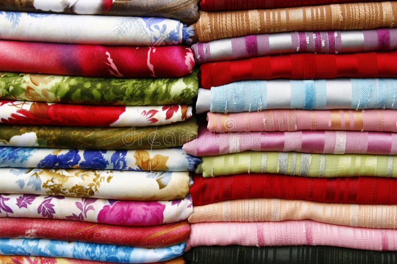 Pile of folded fabrics and shawls. (scarfs) at the market royalty free stock images