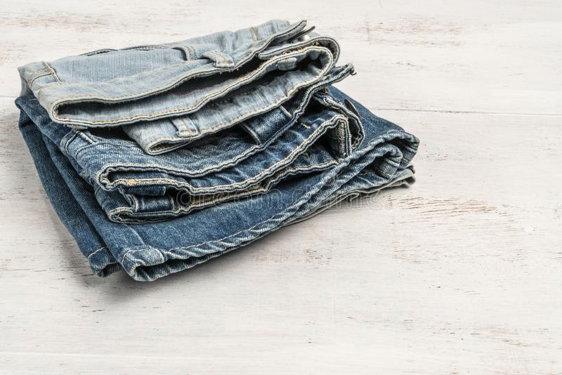 Folded jeans on a wooden background with copy space. Pile of folded jeans on a wooden table with copy space stock photography