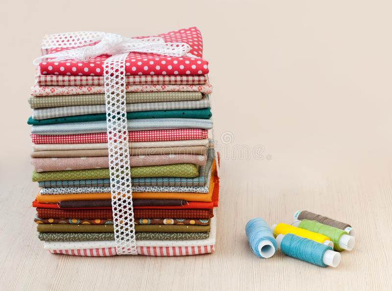 Download Pile Of Folded Textile With Spool Of Thread Stock Photo - Image: 25951610