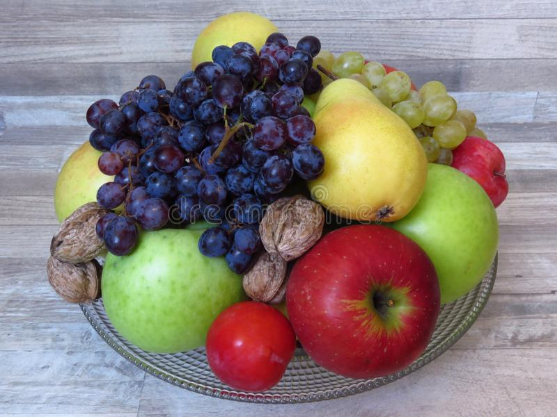 A pile of fresh organic autumn fruit on bleached  oak wood background. Healthy diet / fruit / food. Orchard crop / production / ha. Rvest. Grapes, vivid red and stock photos