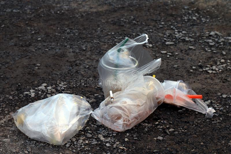 Pile garbage trash drink glass and plastic bag, water cup Juice dirty on floor, plastic waste royalty free stock photos