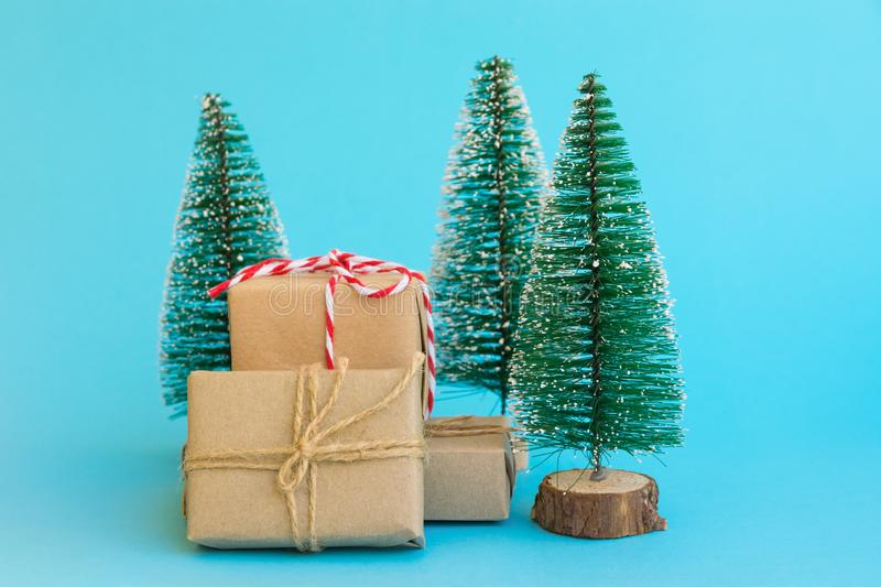 Pile of gift boxes wrapped in craft paper tied with twine red white ribbon Christmas trees on mint blue background. New Year royalty free stock photo