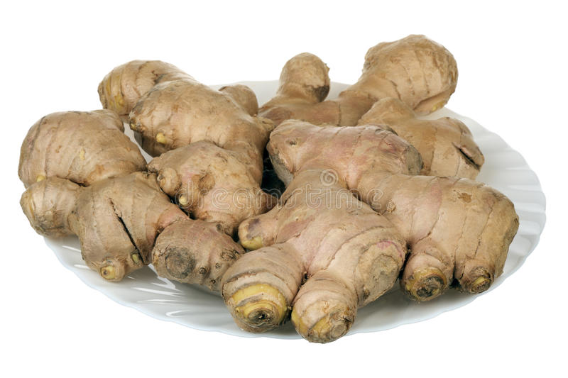Ginger root on a plate. Pile of ginger root on a plate over white background royalty free stock photos