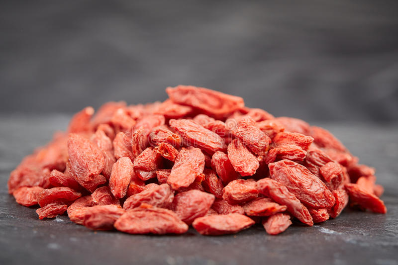Pile of goji berries on a black stone plate royalty free stock image