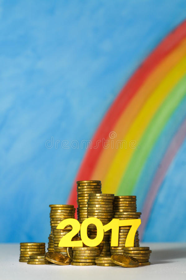 A pile of gold Australian dollar coins with the year 2017 against a blue sky and rainbow background stock images