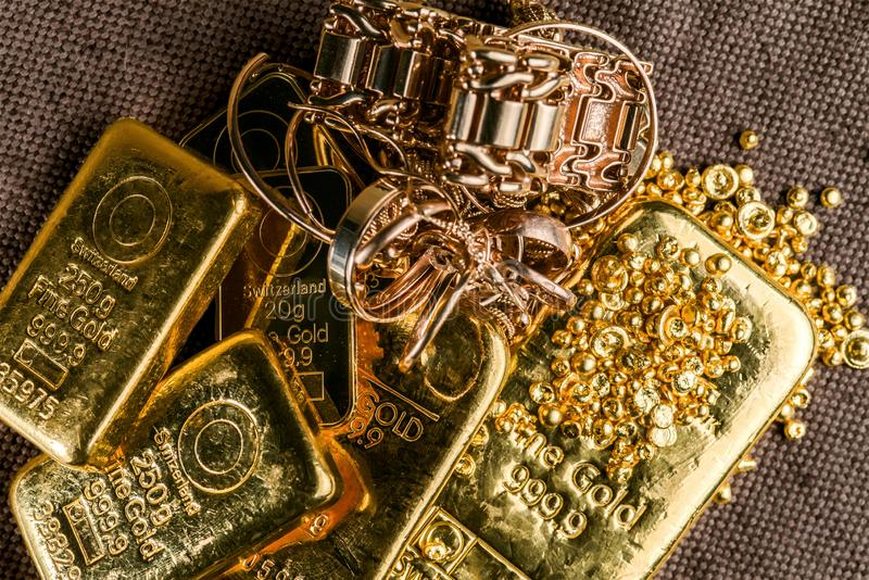 A pile of gold bars gold jewelry and gold granules on the background to the coarse texture of the textile. Selective focus stock image