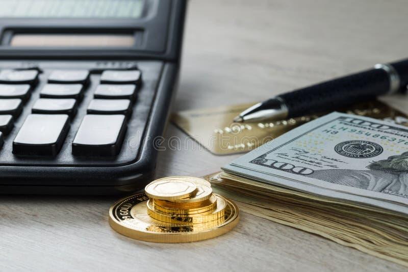 A pile of gold coins, dollar bills, gold credit card, pen and a calculator stock photos