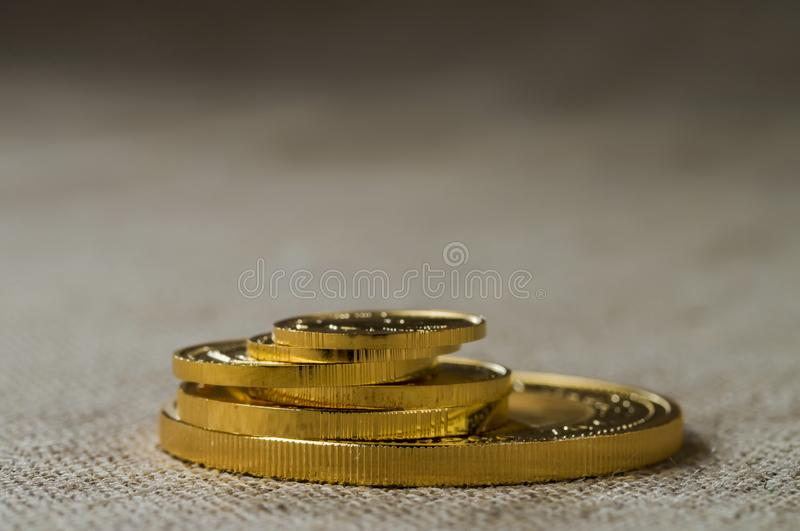 A pile of gold coins of various sizes on a background of rough wood texture royalty free stock photo