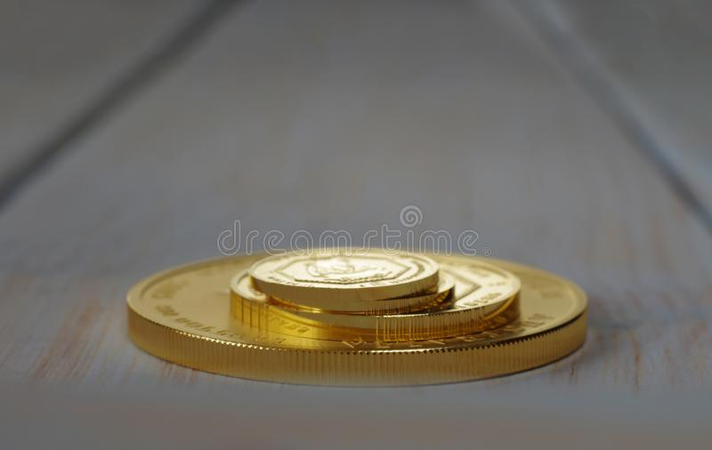 A pile of gold coins of various sizes on a blurred background royalty free stock photos