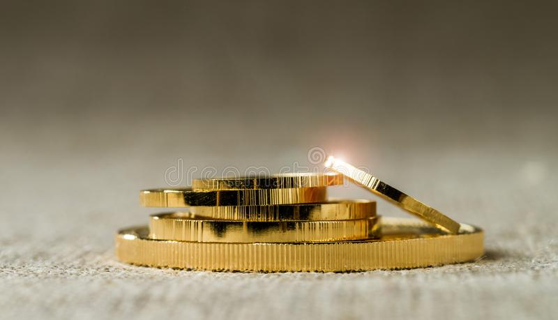 A pile of gold coins of various sizes on a neutral blurred background.  royalty free stock images