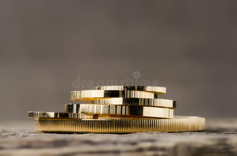 A pile of gold coins of various sizes on a neutral blurred background. Selective focus stock image