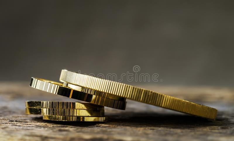 A pile of gold coins of various sizes on a neutral blurred background. royalty free stock photos