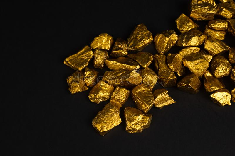 A pile of gold nuggets or gold ore on black background, precious. Stone or lump of golden stone, financial and business concept idea stock photo
