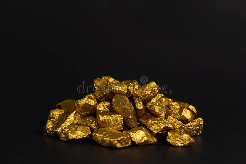 A pile of gold nuggets or gold ore on black background, precious. Stone or lump of golden stone, financial and business concept idea stock image