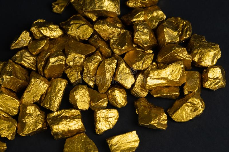 A pile of gold nuggets or gold ore on black background, precious. Stone or lump of golden stone, financial and business concept idea royalty free stock photo