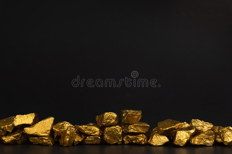 A pile of gold nuggets or gold ore on black background, precious. Stone or lump of golden stone, financial and business concept idea royalty free stock image