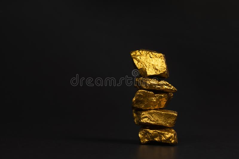 A pile of gold nuggets or gold ore on black background, precious. Stone or lump of golden stone, financial and business concept idea stock photography
