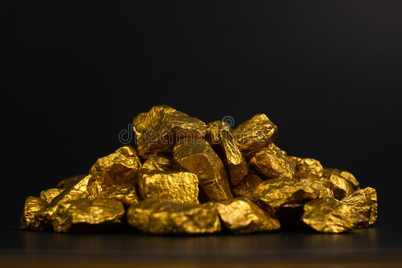 A pile of gold nuggets or gold ore on black background, precious. Stone or lump of golden stone, financial and business concept idea stock images