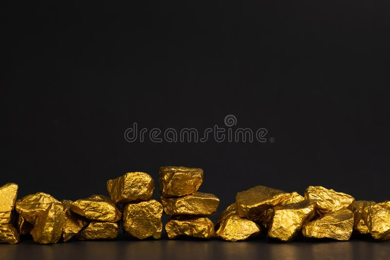 A pile of gold nuggets or gold ore on black background, precious stone or lump of golden stone, financial and business concept royalty free stock image