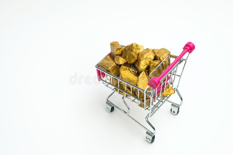 Pile of gold nuggets or gold ore in shopping cart or supermarket. Trolley on white background, precious stone or lump of golden stone, financial and business stock images