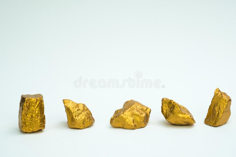 A pile of gold nuggets or gold ore on white background, precious. Stone or lump of golden stone, financial and business concept idea stock images