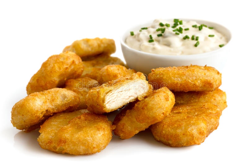 Pile of golden deep-fried battered chicken nuggets with bowl of royalty free stock images