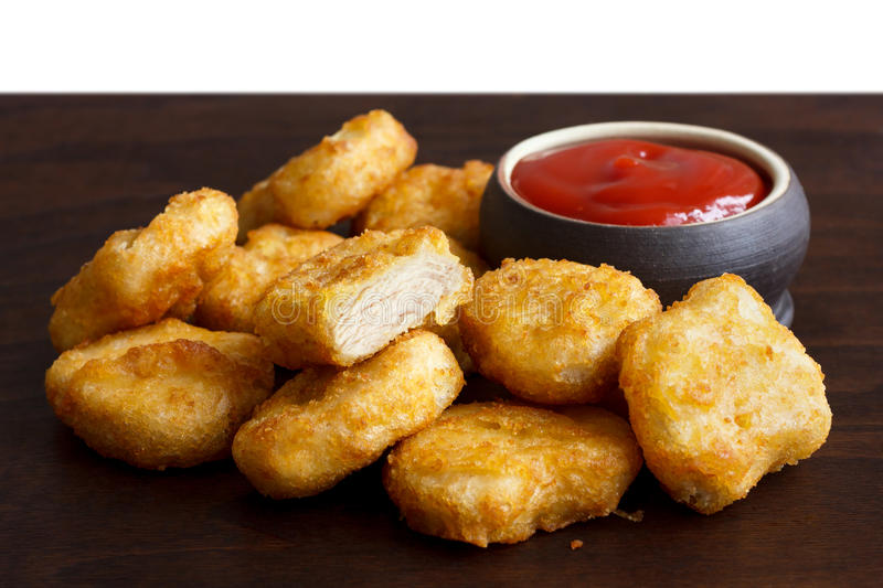 Pile of golden deep-fried battered chicken nuggets with empty ru stock photo