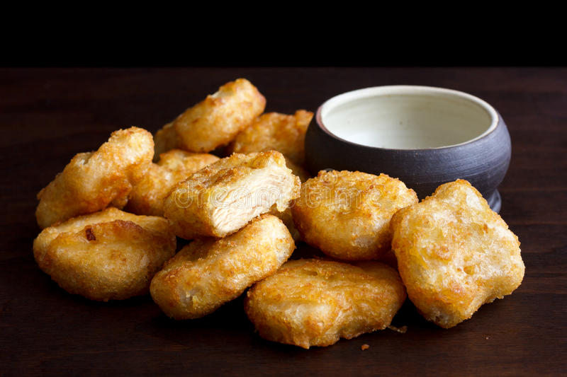 Pile of golden deep-fried battered chicken nuggets with empty ru royalty free stock images