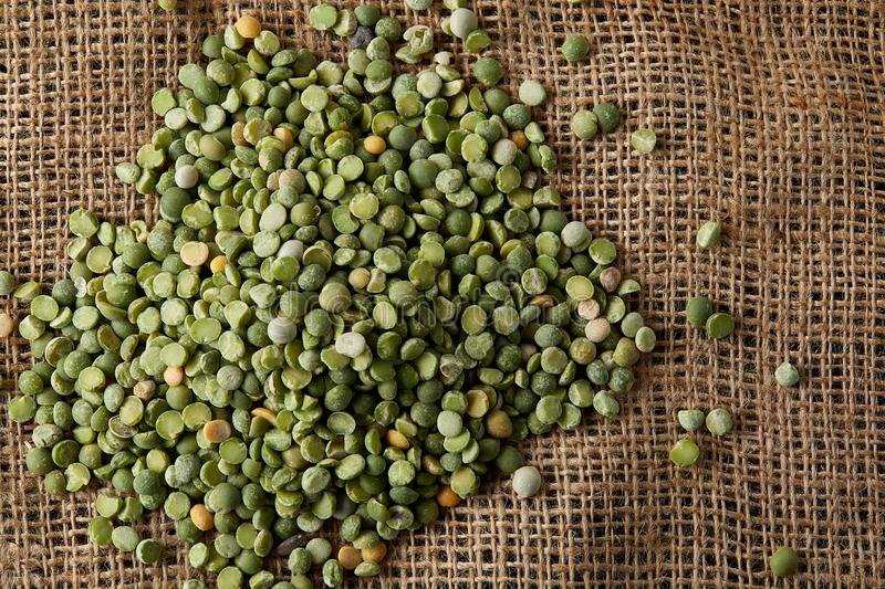 Pile of green peas on burlap tablecloth, close-up, top view, selective focus, shallow depth of field. stock photography