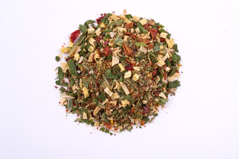 A pile of a green spice mix dried vegetables and herbs. Isolated on white background. stock photography